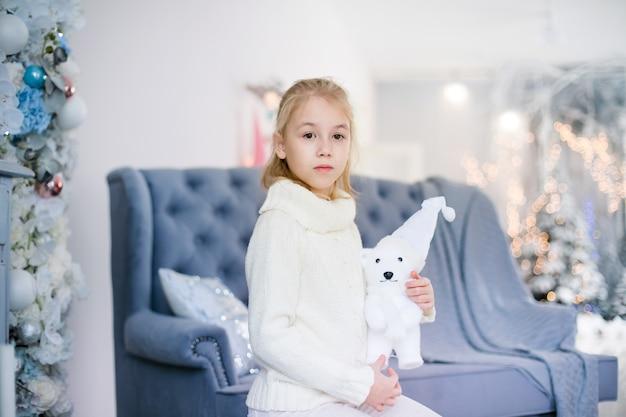 Charmante petite fille blonde en pull chaud blanc avec ourson assis sur le fauteuil bleu