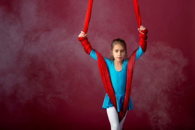 Charmante petite fille dans un costume de gymnastique bleu préparé pour la performance avec un ruban aéré rouge sur fond rouge-pâle. concept de sports acrobatiques pour enfants. espace publicitaire