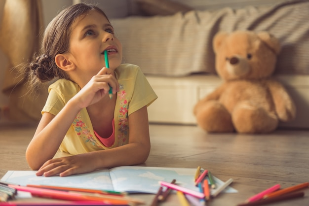 Charmante petite fille dessine, regarde ailleurs.