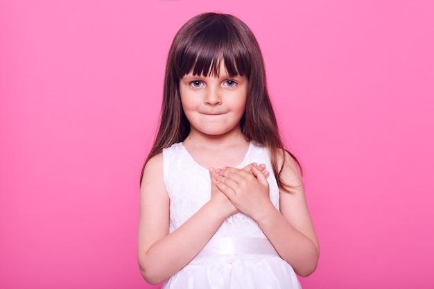 Charmante petite fille honnête vêtue d'une robe blanche à l'avant, gardant les mains sur la poitrine, a une expression reconnaissante, jurant, prometteuse, isolée sur un mur rose