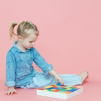 Une charmante petite fille en jean sur fond rose