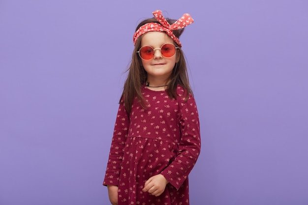 Charmante petite fille à la mode hipster habillée en robe bordeaux