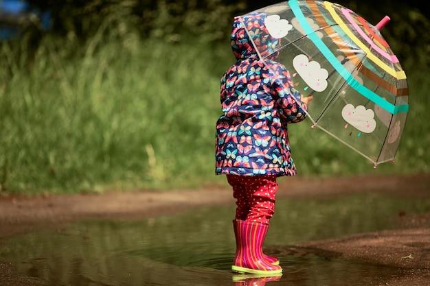 Charmante petite fille avec un parapluie s'amuse debout dans des bottes en caoutchouc dans la piscine après la pluie