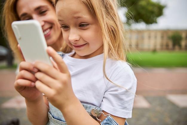 Charmante petite fille regardant sur l'écran du téléphone portable en se tenant devant une femme adulte