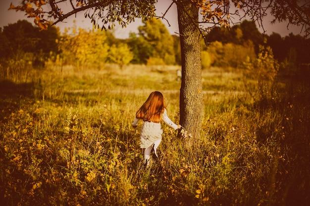 Charmante petite fille s'exécute dans la haute herbe d'automne