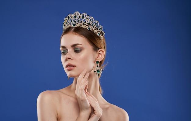 Charmante princesse avec un diadème sur la tête avec des boucles d'oreilles modèle de maquillage fond bleu. photo de haute qualité