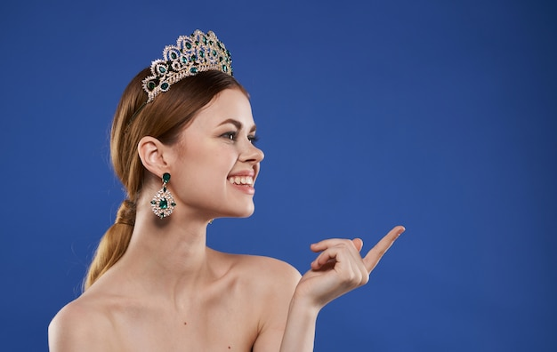 Charmante princesse avec un diadème sur la tête, boucles d'oreilles, modèle de maquillage