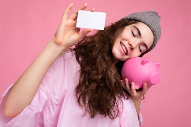 Charmante souriante joyeuse jeune femme brune frisée portant une chemise rose et un chapeau gris isolé sur