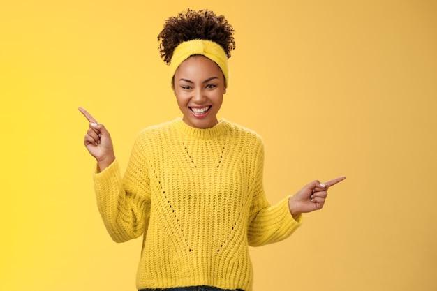 Charmante tendre romantique jeune femme afro-américaine des années 20 souriante amicale satisfaite riant belle caméra pointant vers le haut sur le côté montrer les choix de produits dans les deux sens, debout sur fond jaune.