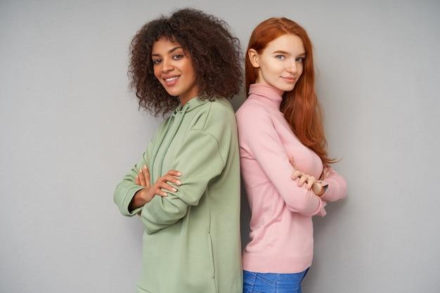Charmantes jeunes femmes charmantes vêtues de vêtements décontractés, pliant les mains sur la poitrine et à la recherche positive avec un sourire doux, isolé sur un mur gris