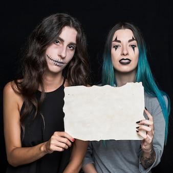 Charmantes jeunes femmes avec une feuille de papier