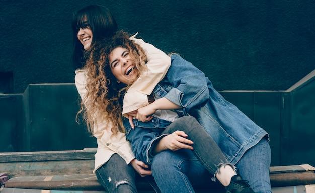 Charmantes jeunes sœurs embrassant et riant tout en s'amusant en plein air dans la ville.