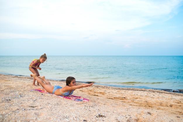 De charmantes petites filles font des exercices de gymnastique sur le sable de la mer