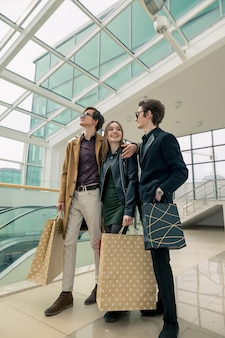Charmants accros du shopping avec des sacs en papier discutant de quelque chose que la scie dans le centre commercial