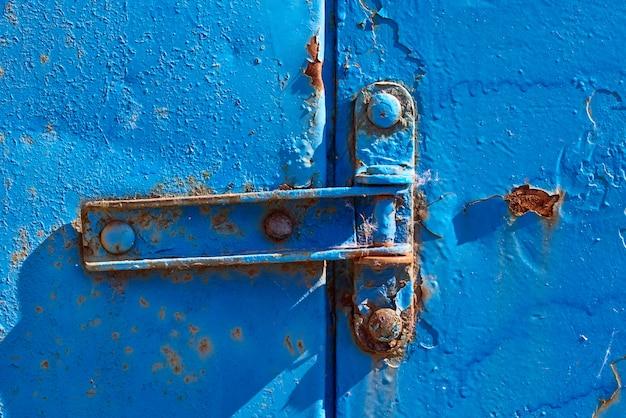 Charnière rouillée sur la vieille porte en métal rouillé bleu, gros plan