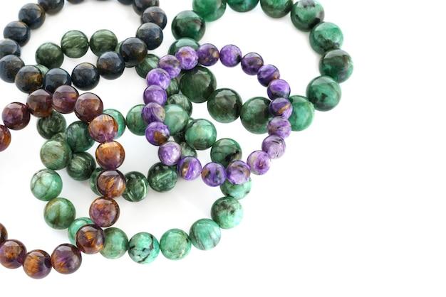 Charoid seraphinite cacoxenite pietersite et emerald perles en bracelets sur fond blanc