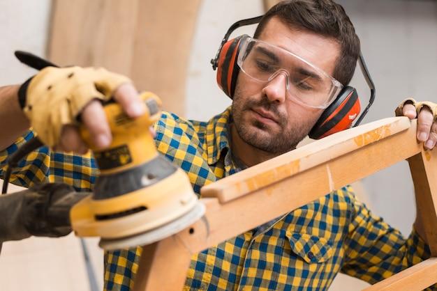 Charpentier adoucissant les bords de meubles en bois avec ponceuse électrique