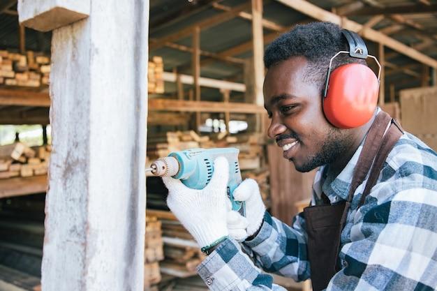 Charpentier d'afro-américain utilisant la perceuse électrique