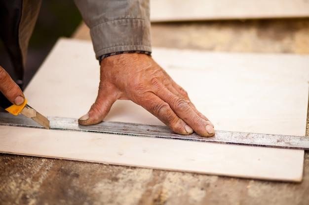 Charpentier âgé à l'aide d'une règle pour tracer une ligne sur une planche.