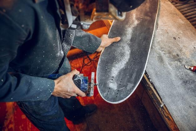 Charpentier à l'aide d'une scie circulaire pour couper des planches en bois