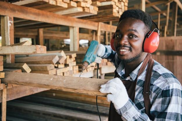 Charpentier américain d'afrique utilisant une perceuse électrique sur bois