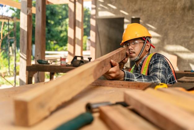 Le charpentier asiatique examine visuellement l'exactitude du bois au chantier de construction.