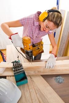 Charpentier au travail à l'aide d'une perceuse à main