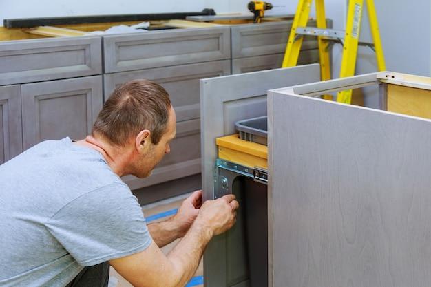 Un charpentier construit une corbeille à tiroirs dans la cuisine