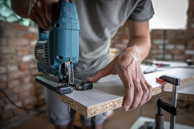 Un charpentier coupe un bois avec une scie sauteuse électrique, travaillant avec un arbre.