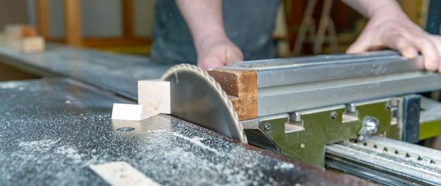 Charpentier coupe une planche de bois sur une scie circulaire