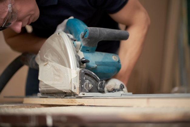 Le charpentier dans les gants blancs travaille sur un puzzle