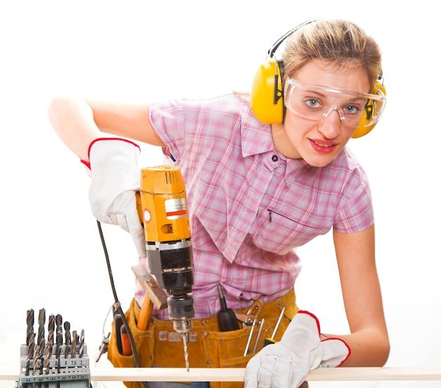 Charpentier féminin au travail à l'aide d'une perceuse à main