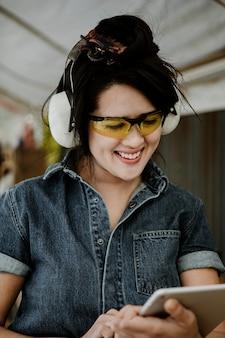 Charpentier féminin joyeux avec des écouteurs protecteurs à l'aide d'une tablette dans un atelier