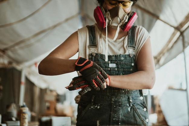 Charpentier féminin portant un équipement de protection individuelle