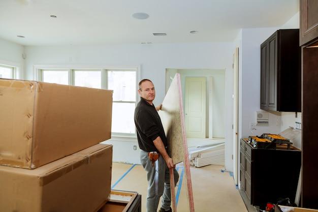 Charpentier installant des armoires et des comptoirs dans la cuisine.