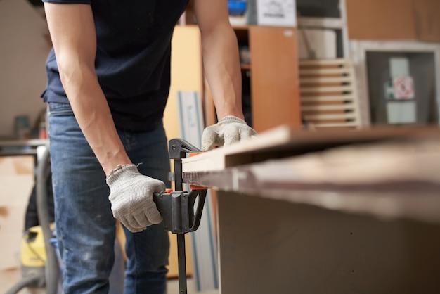Charpentier masculin dans le conseil de brides de gants dans le vice à l'atelier