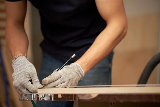 Le charpentier masculin tient le conseil étroit dans son atelier