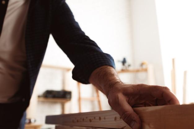 Charpentier masculin travaillant avec une barre en bois dans un atelier