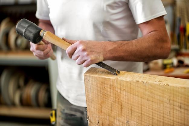 Charpentier ou menuisier travaillant avec un ciseau