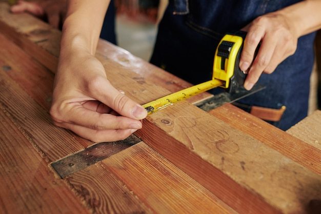 Charpentier mesurant la planche de bois