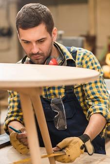 Un charpentier mesure la table en bois avec une règle