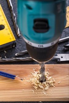 Charpentier, perçage du bois à l'aide d'une perceuse portative