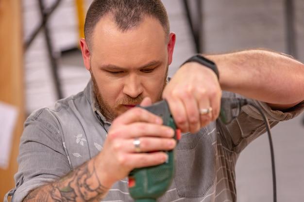 Charpentier avec perceuse électrique forage planche de bois à l'atelier