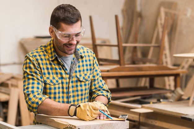 Charpentier professionnel souriant, mesurant le bloc de bois avec une règle