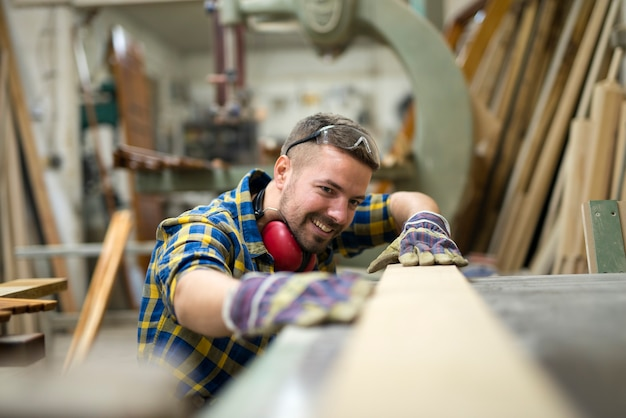 Charpentier professionnel vérifiant la douceur du produit en bois en atelier