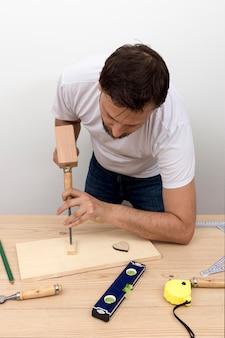 Charpentier qualifié à l'aide d'outils sur bois