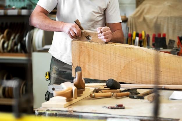 Charpentier rabotant un bloc de bois avec une raboteuse
