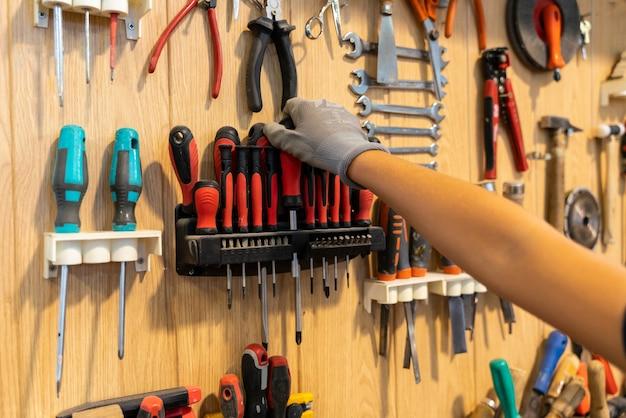 Charpentier récupérant un outil de sa boîte à outils dans une menuiserie.