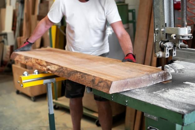 Charpentier sciant une planche de bois sur une scie à ruban