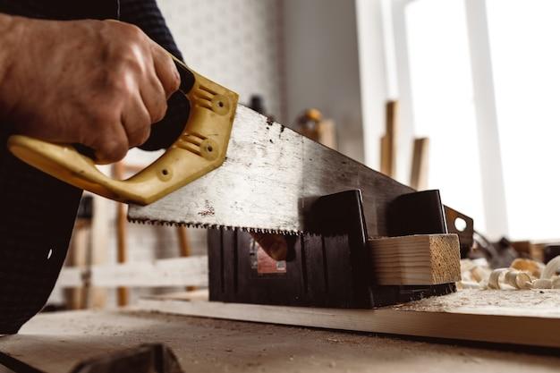 Le charpentier scie un bloc de bois dans un atelier